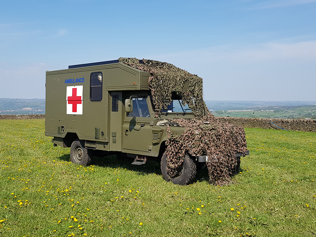 land rover ambulance campervan in field